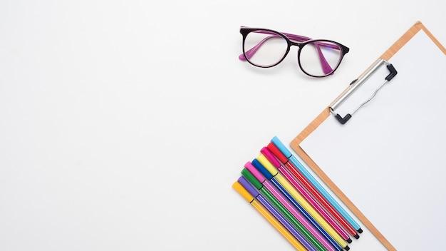 テーブルトップビューのコピースペースにカラーペンとメガネの板紙