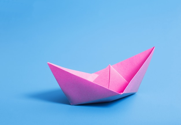 Paper boat on blue paper wall