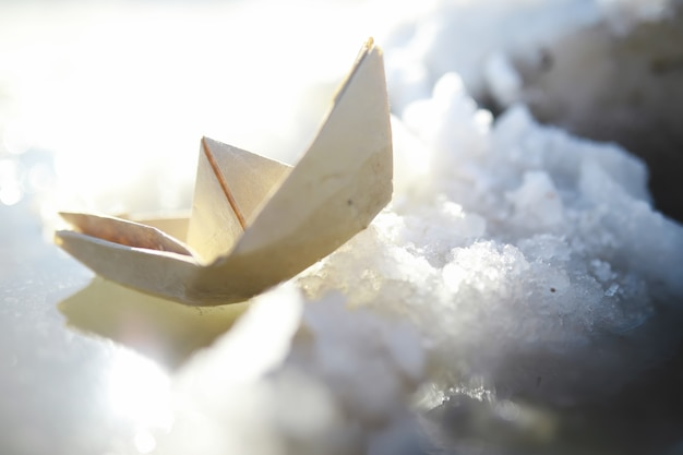 通りの水の中の紙の船。早春のコンセプト。雪解けと水の波で折り紙のボート。