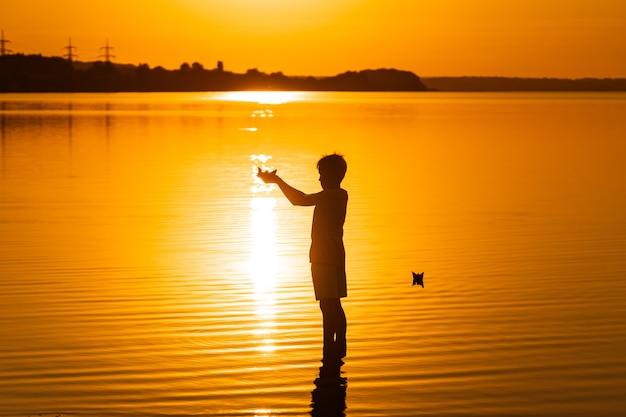 종이 배는 아이의 손에 있습니다. 아름다운 주황색 일몰