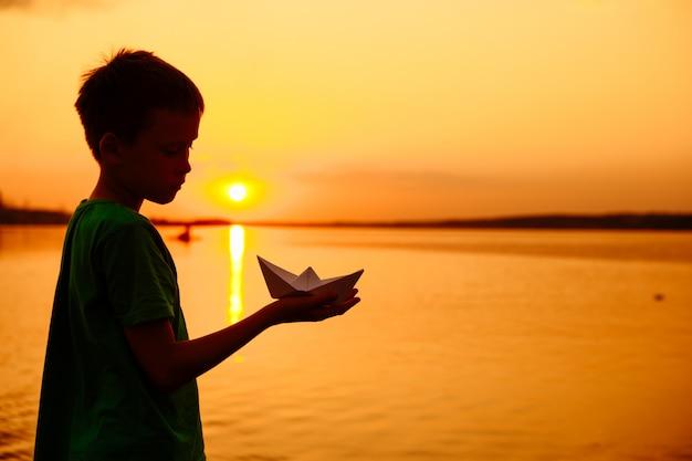 종이 보트는 어린이의 손에 있습니다. 아름다운 여름 일몰. 종이 접기