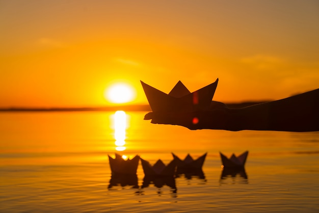 Paper boat is on a palm of boy. four paper origami which float in the river at sunset