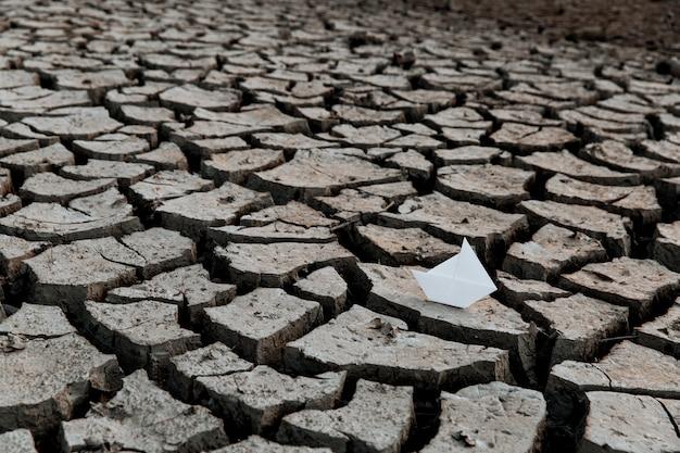 Бумажный кораблик на сухом озере концепция засухи и кризисной среды