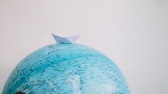 Paper boat on globe