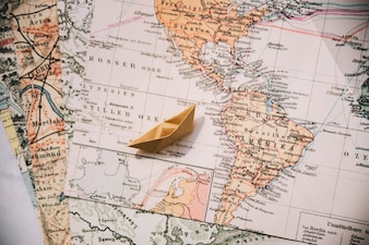 Paper boat on maps