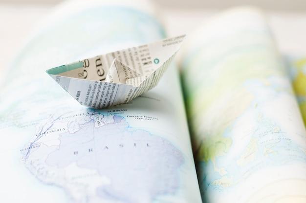 Бумажный кораблик поверх карт