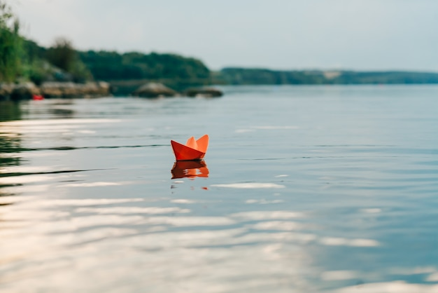 A paper boat sails by the river in the summer. it has an orange color and floats downstream along the shore