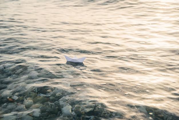 紙の船は、青い水面の海に出航します。