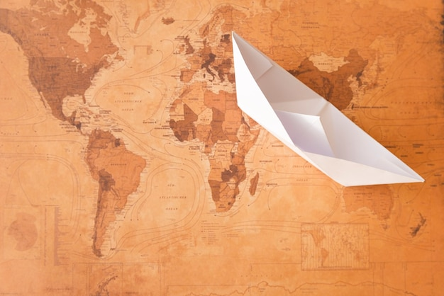 Paper boat on sepia map