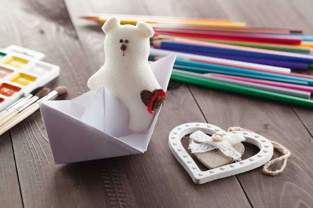 Paper boat and soft toy on wooden table