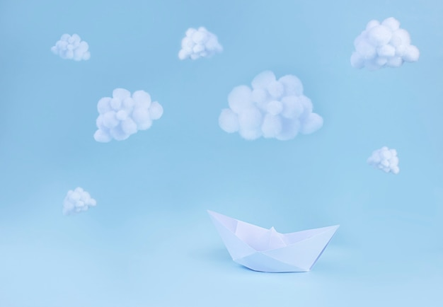 Paper boat and white fluffy clouds on light blue surface