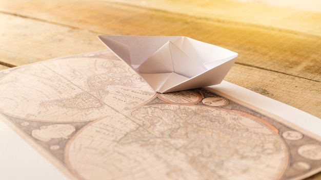 Paper boat with defocused old map