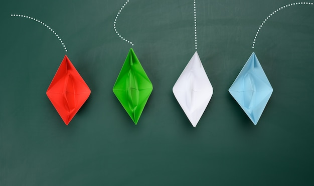 Paper boats sail in different directions on a green background. concept of leadership, achieving goals and disunity, top view