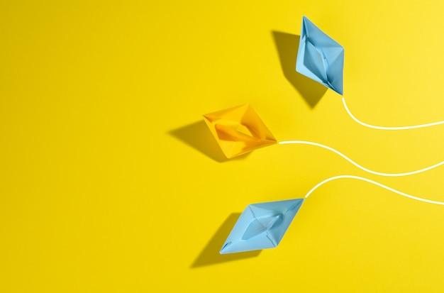 Бумажные кораблики плывут в разные стороны по желтой поверхности. концепция лидерства, достижения целей и разобщенности, вид сверху