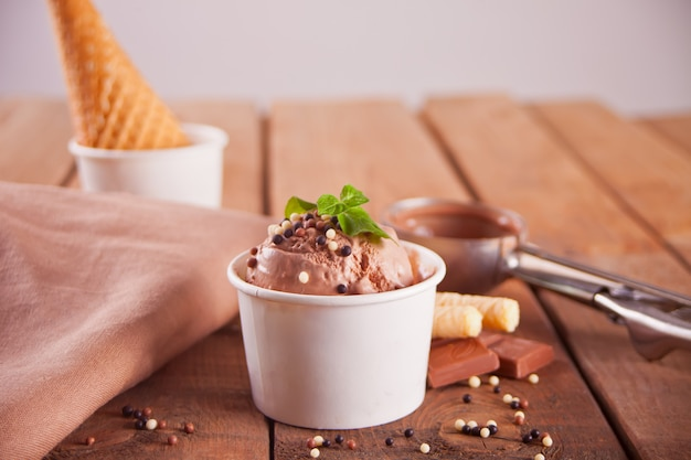 Paper bowl of chocolate ice cream, waffle cone and spoon for ice cream