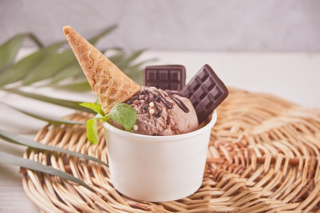 Paper bowl of chocolate ice cream with small waffle cone and chocolate