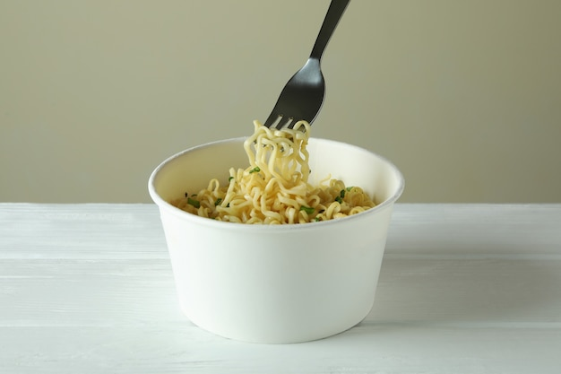 Paper bowl and fork with cooked noodles on white wooden table