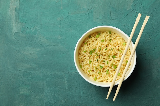 Paper bowl with noodles and chopsticks on green textured