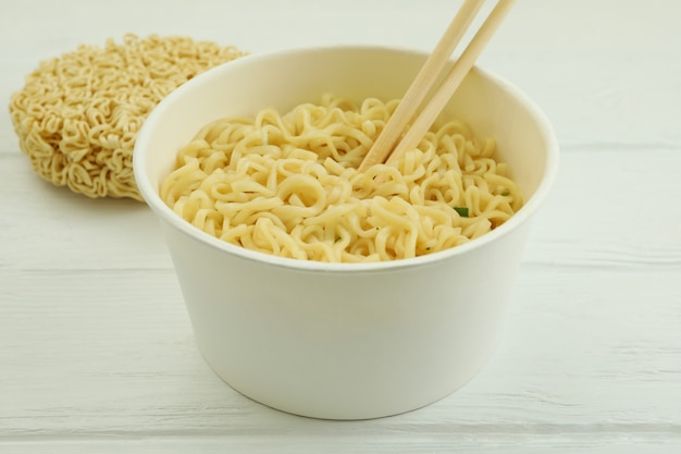 Paper bowl with noodles and chopsticks on white wooden