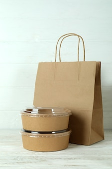 白い木製のテーブルの上の紙のボウルと紙袋