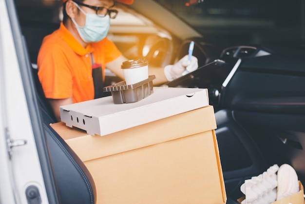 Paper box and coffee cup with blured delivery man employee checking list on clipboard