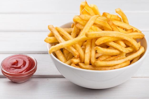 흰색 판자 배경 위에 식욕을 돋우는 감자튀김 더미가 있는 종이 상자