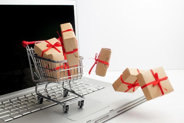 ノートパソコンのキーボードのショッピングカートの紙箱。 eコマース、商品やサービスをオンラインで売買する取引に関するアイデア。