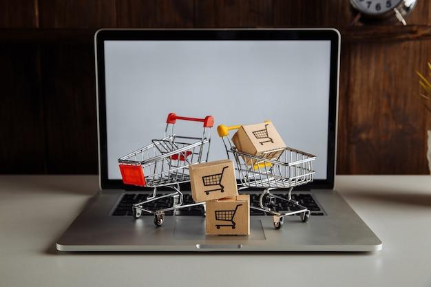ノートパソコンのキーボードのスーパーマーケットのカートの紙箱。オンラインショッピングと配達のコンセプト。