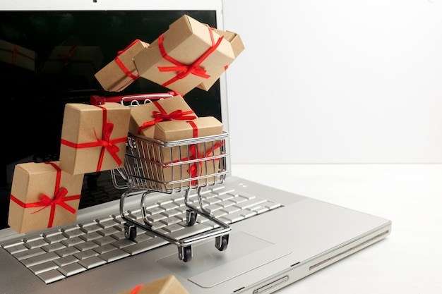 Paper boxes in a shopping cart on a laptop keyboard. ideas about e-commerce, a transaction of buying or selling goods or services online.