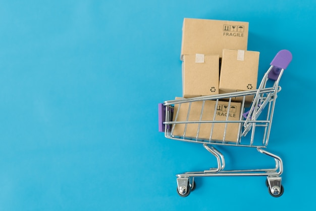 Paper boxes in a trolley on blue background