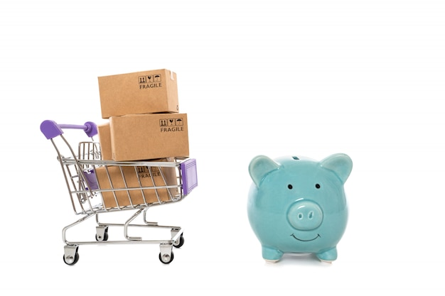Paper boxes in a trolley with piggy bank on white background.concept of savings online shopping