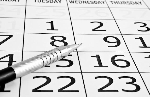 日付とペン付きの紙のカレンダー