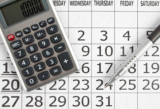 ペンと電卓付きの紙のカレンダー