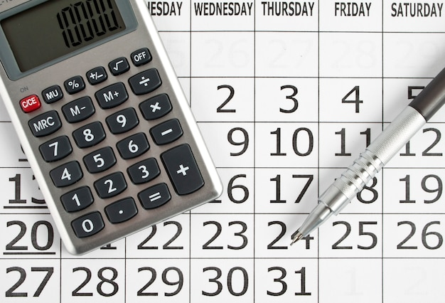 Paper calendar with pen and calculator