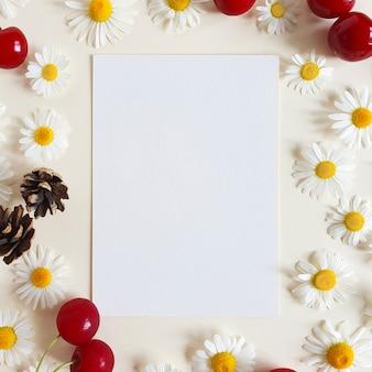 Бумага, ромашки, ягоды вишни и еловые шишки на фоне слоновой кости.