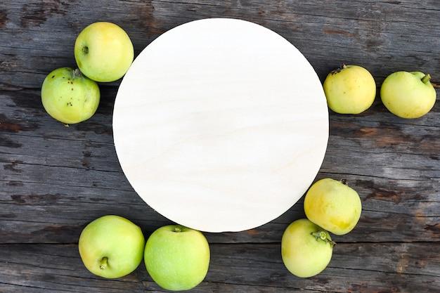 素朴な木製のテーブルに紙のカードとジューシーな青リンゴ