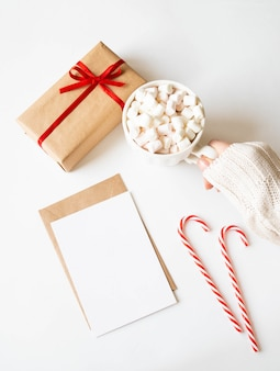 Paper card for letter, envelope, xmas decoration and female hand holds a white mug with hot drink and marshmallows on white background. top view. copy space