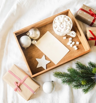 Paper card for letter in wood tray, mug with hot drink and marshmallows and xmas decoration. flat lay for merry christmas or happy new year.