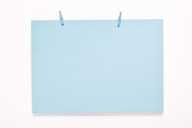 Бумажная карточка на прищепке на белом фоне