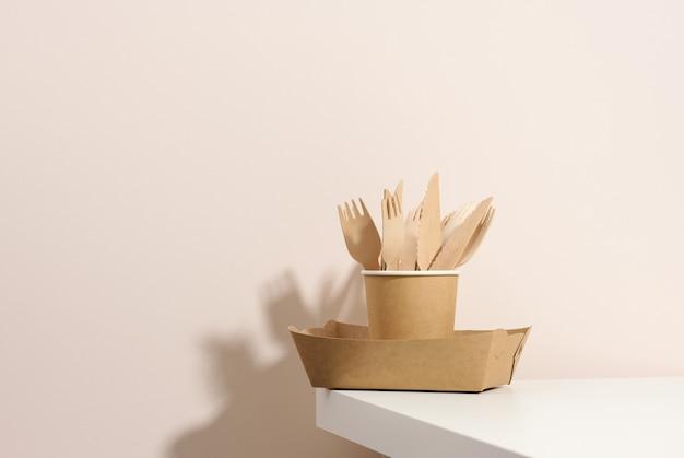 Бумажные картонные коричневые тарелки и чашки, деревянные вилки и ножи на белом столе, бежевом фоне. экологичная посуда, без отходов