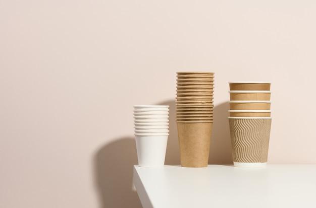 Бумажные картонные белые и коричневые чашки для кофе и чая, бежевый фон. экологичная посуда, без отходов