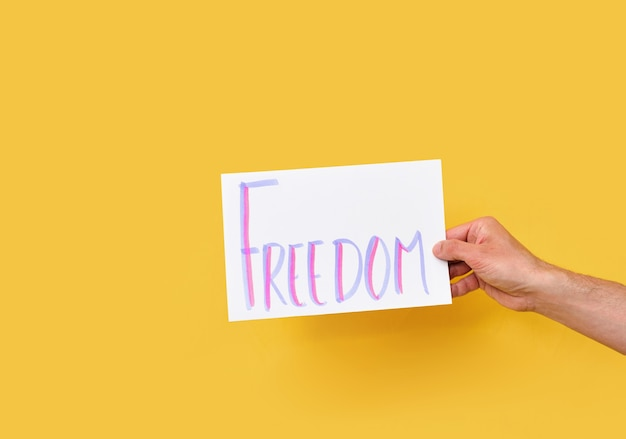 Бумажный картон со словом свобода на изолированном желтом фоне