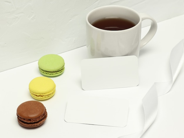 Paper cards on white background with macaron, ribbon and cup of coffee