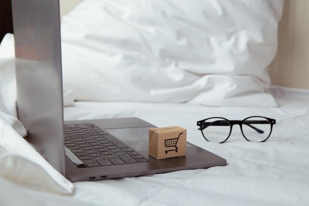 침실에서 노트북 키보드에 종이 상자 또는 소포. 온라인 웹에서 쇼핑 서비스를 제공하고 택배를 제공합니다.