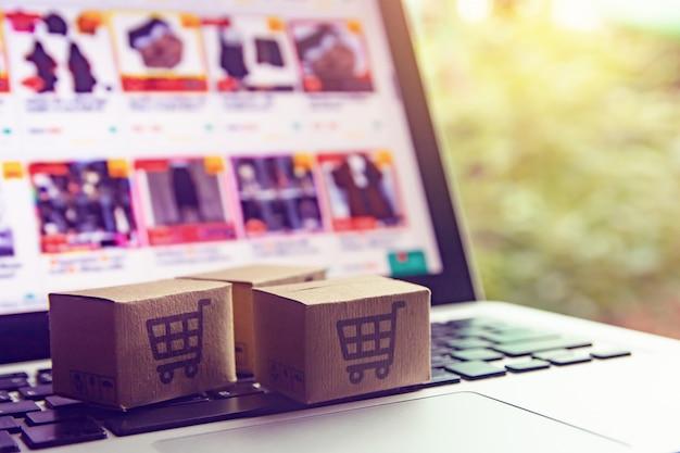 노트북 키보드에 장바구니 로고가있는 종이 상자 또는 소포. 온라인 웹 쇼핑 서비스 및 택배를 제공합니다.