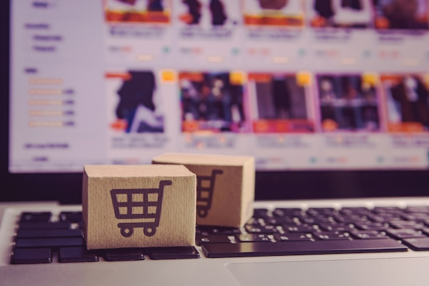 노트북 키보드에 쇼핑 카트 로고가있는 종이 상자.
