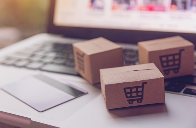 Paper cartons with a shopping cart logo and credit card on a laptop keyboard