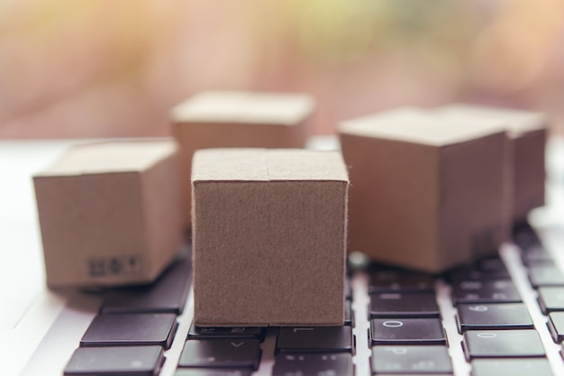 Paper cartons with a shopping cart logo on a laptop keyboard.