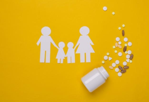 Семейство бумажных цепочек, бутылочные таблетки на желтом, концепция медицинского страхования