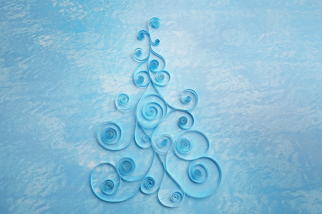 Paper christmas tree on blue surface